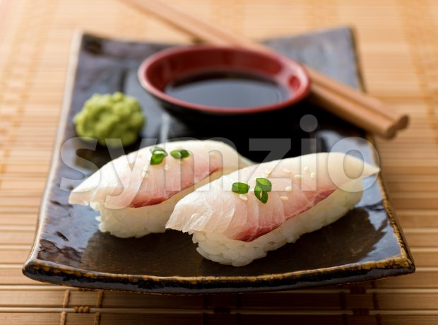 A delicious white fish nigiri-zushi with rice, wasabi paste, and japanese soy garnished with green onion and sesame seeds.