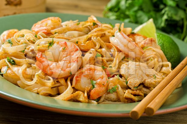 A plate of spicy pad thai with chicken and shrimp with chopsticks.