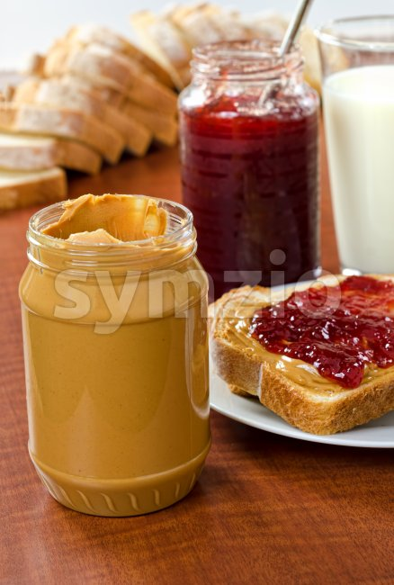 Peanut butter and jelly bottles with bread and a glass of milk.