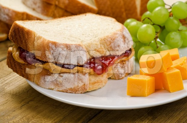 A nutritious peanut butter and jelly sandwich with cheddar cheese and grapes.