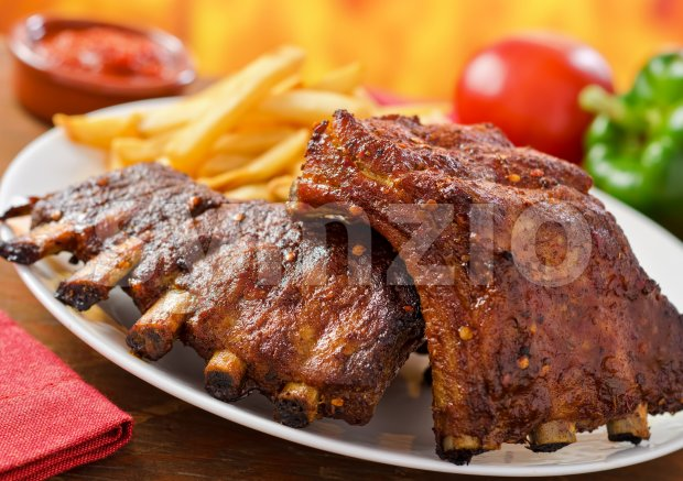 Barbecued pork baby back ribs against a hardwood fire background.