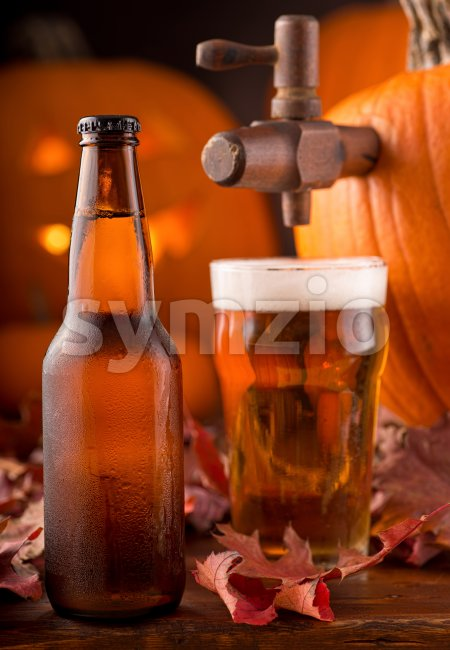 A bottle and glass of cold creamy pumpkin ale.