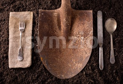 Rusted shovel on soil background with fork, knife, spoon, and napkin. Stock Photo