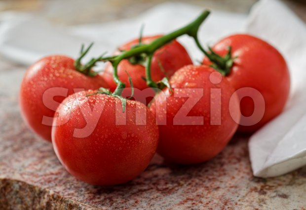 Vine ripened red tomatoes against a marble background.