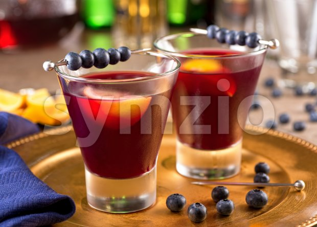 Two delicious blueberry cocktails with blueberry juice and lemon.