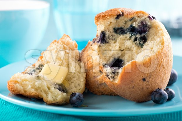 A delicous freshly baked blueberry muffin with melted butter.