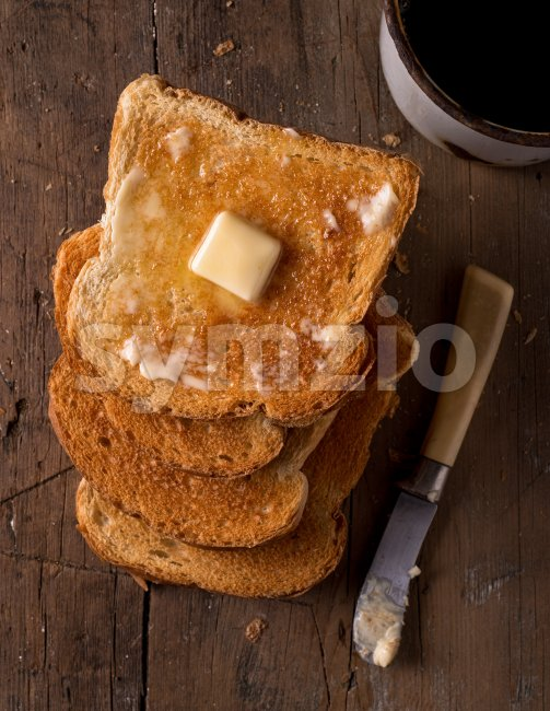 Crusty buttered toast slices on a rustic tabletop with coffee.