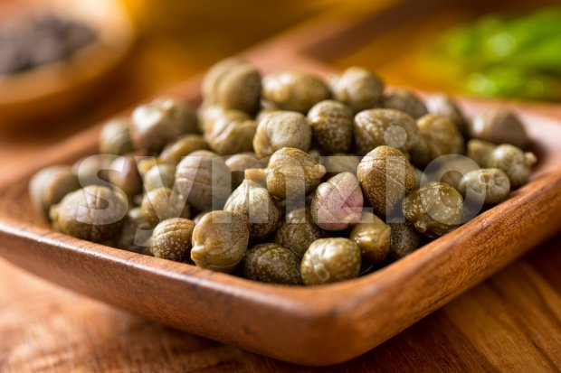 Pickled capers in a wooden serving bowl with basil and black peppercorns.
