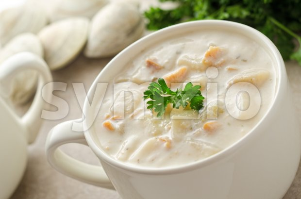 A bowl of creamy New England clam chowder with whole clams and parsley.