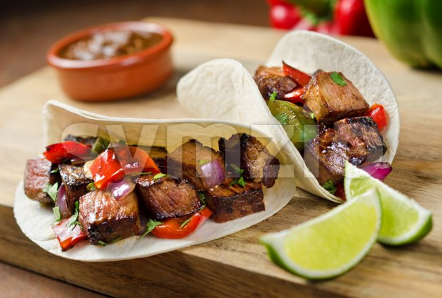 Two beef fajitas with red onion, peppers, cilantro, and lime.