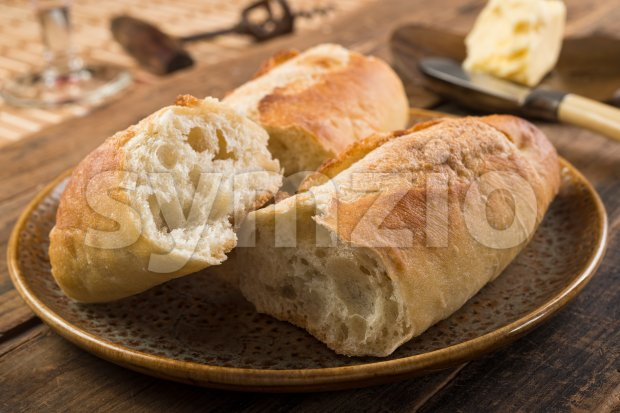 French bread baguette and butter on a rustic wooden tabletop.