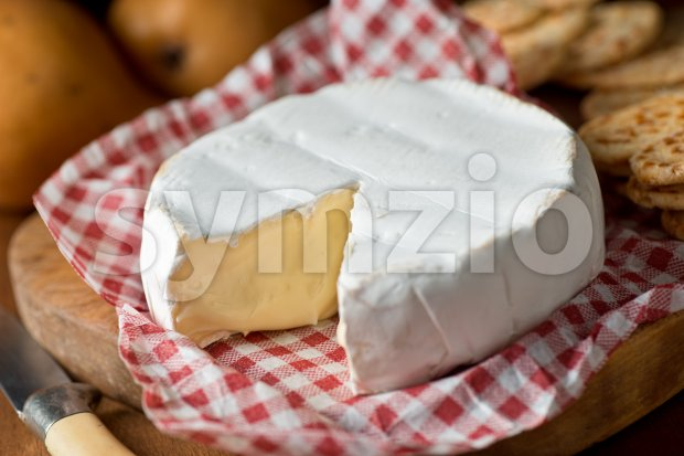 Delicious creamy wheel of brie cheese with crackers and pears.